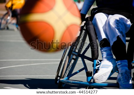 paralympic games, basketball player  in the wheelchair, motion blur on ball - stock photo