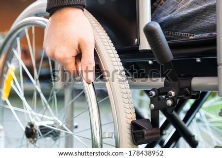 Paralyzed man using his wheelchair - stock photo