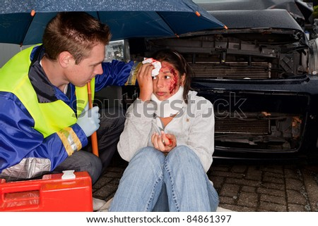 Paramedic caring for an injured woman under an umbrella - stock photo