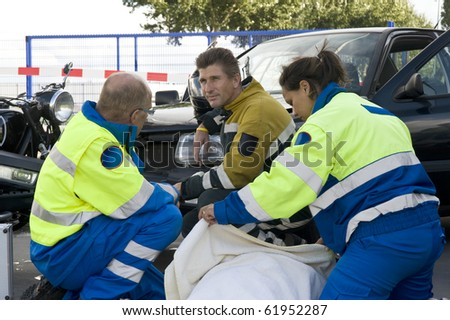 paramedic covers a patient with a blanket to protect her from the cold. - stock photo