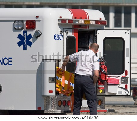 paramedic pulling stretcher from ambulance - stock photo