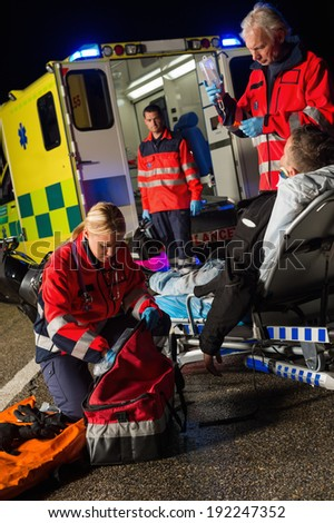 Paramedic team assisting injured motorbike man driver at night