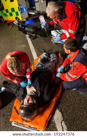 Paramedical team helping injured motorcycle man driver at night - stock photo