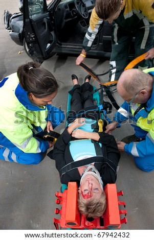 Paramedics and a fireman strapping an injured woman to a stretcher, seen from above - stock photo