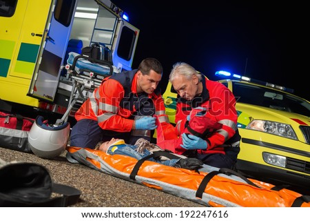 Paramedics giving first-aid to injured motorbike woman driver at night - stock photo