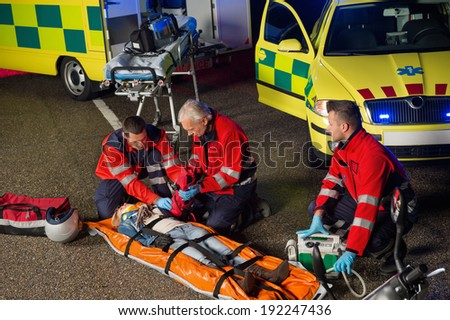 Paramedics helping injured woman motorbike driver on stretcher at night