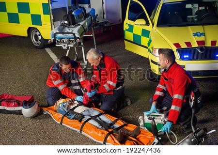 Paramedics helping injured woman motorbike driver on stretcher at night - stock photo