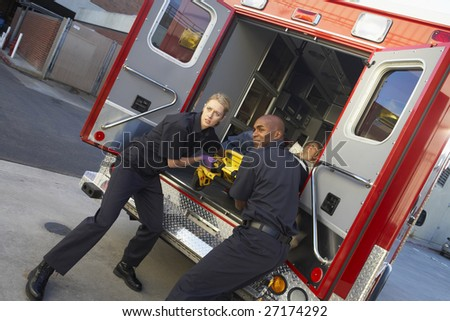 Paramedics preparing to unload patient from ambulance - stock photo