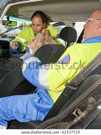 Paramedics providing first aid to an injured woman in a car - stock photo