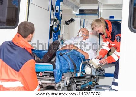 Paramedics putting patient man oxygen mask in ambulance car - stock photo