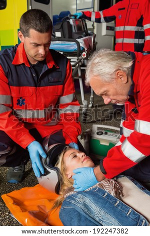Paramedics removing helmet from injured woman motorbike driver at night - stock photo