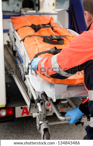 Paramedics rolling out gurney from emergency truck - stock photo