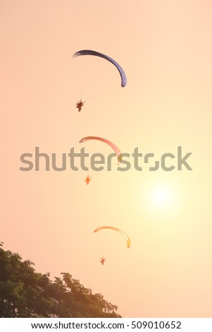 Paramotor fly in sunset sky