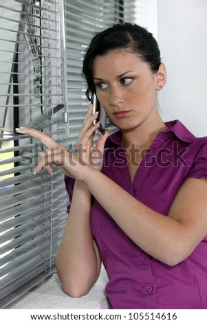 Paranoid woman looking through the window blinds - stock photo