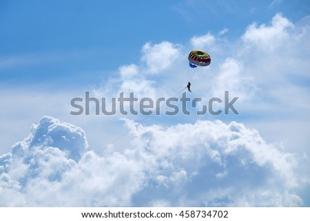 Parasailing against a blue sky and cloud.