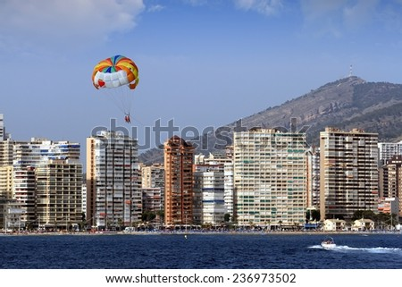 Parasailing flying over the beach of Benidorm city. - stock photo