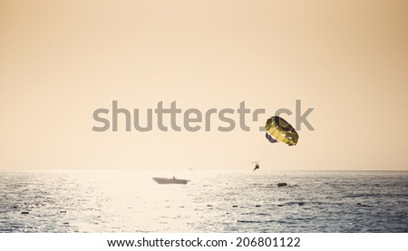 Parasailing on parachute over water at sunset  - stock photo