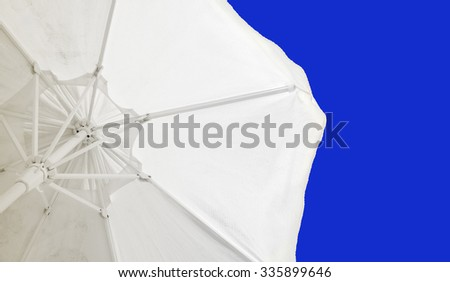 Parasol against the blue clear sky - stock photo
