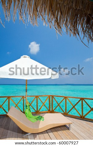 Parasol and chaise lounge on a terrace of water villa, Maldives - stock photo