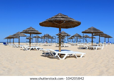 Parasol and sun loungers on the beach sand, Tavira island, Algarve. Portugal