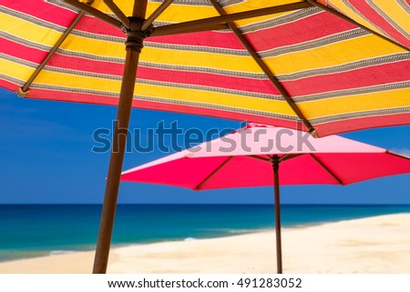 Parasol by the beach against blue sky background.