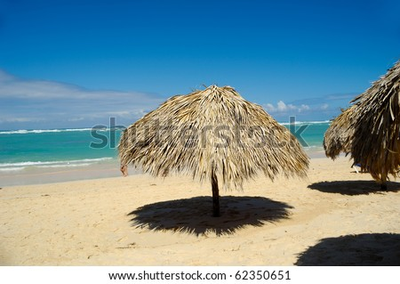 Parasol made out of palm leafs on beach. - stock photo