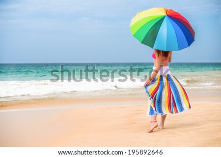 Parasol. Young woman under parasol on a sunny beach