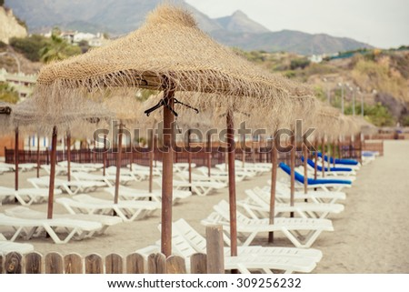 Parasols and empty deckchairs on the Nerja beach.  Spain - stock photo