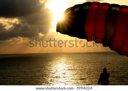 Paratrooper against sunset background - stock photo