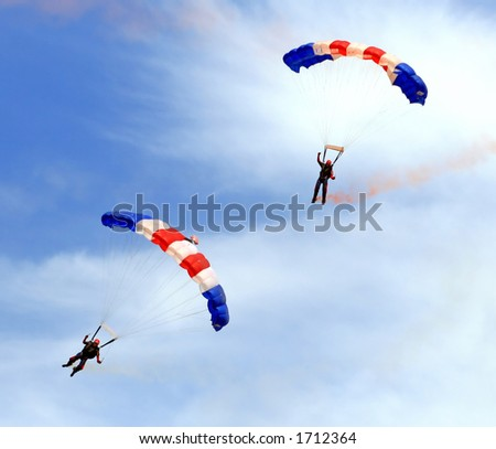 Paratroopers descending in a military skydiving parachute demonstration - stock photo
