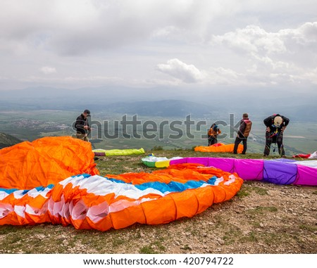 Paratroopers setting up parachutes against nature background - stock photo