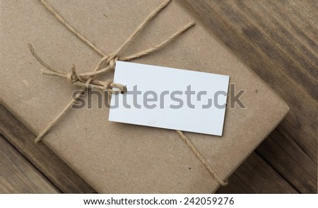 parcel a price tag wrapped in brown kraft paper on wooden table closeup - stock photo