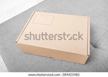 Parcel. Cardboard box on the sofa in the interior. - stock photo