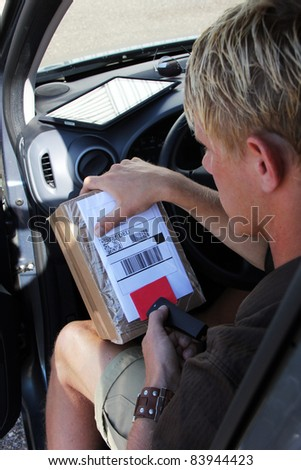 Parcel delivery with  parcel label barcode scanning - stock photo