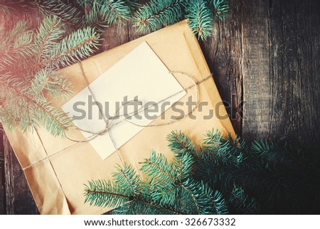 Parcel in Vintage Envelope with Fir-tree Branches on a Wooden Background. Toned - stock photo