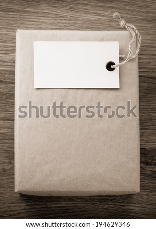 parcel wrapped packaged box on wooden background - stock photo