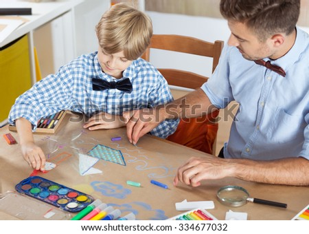 Parent and child drawing together at home - stock photo