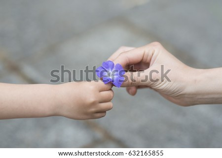 Parent and child handing blue flower