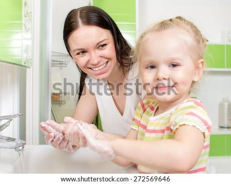Parent helps kid hands washing - stock photo