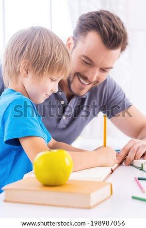 Parent support. Side view of cheerful young father helping his son to do homework while sitting at the table together with green apple laying on the foreground - stock photo