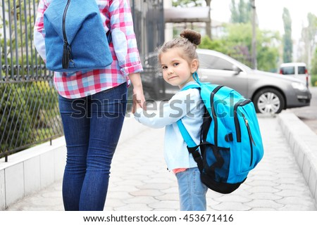 Parent taking child to school - stock photo