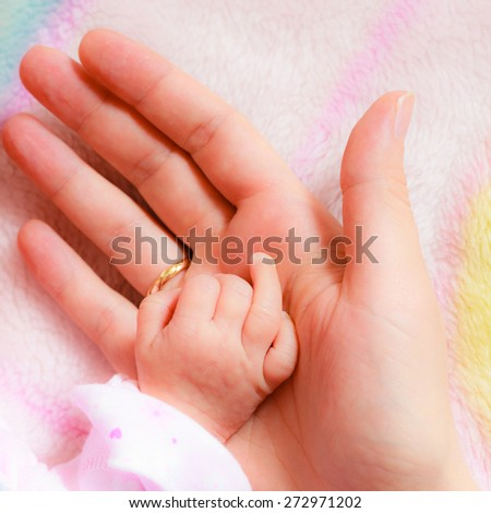 Parenting and love concept. Closeup newborn baby holding his mothers finger. Square format - stock photo