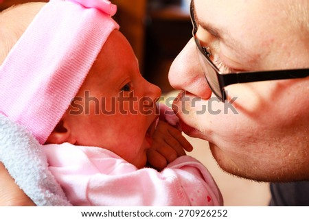 Parenting concept. Father holding delicate his newborn baby girl and kissing, at home - stock photo