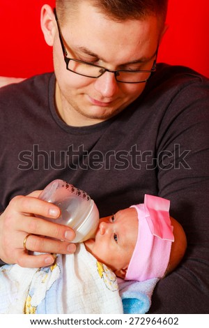 Parenting concept. Happy young father feeding newborn baby girl with milk bottle on couch at home