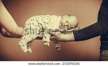 Parenting family and love concept. one month old baby girl sleeping in the comfort of parents arms, vintage filter - stock photo