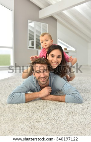Parents and baby girl laying on carpet,  - stock photo