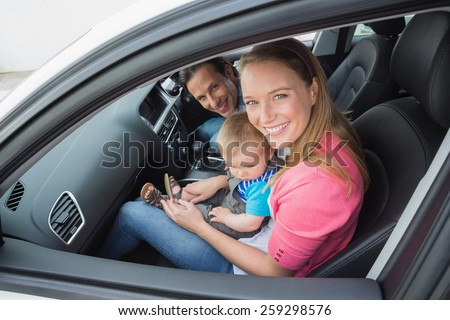 Parents and baby on a drive in their car - stock photo