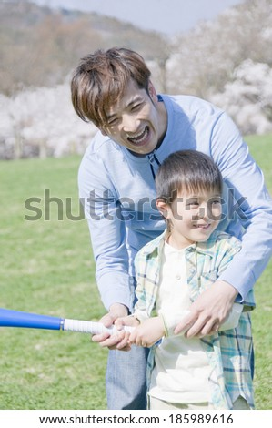 parents and child holding a bat together - stock photo