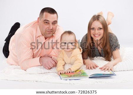 Parents and child reading picture book. studio shot. - stock photo