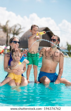 Parents and children enjoying their time in the pool - stock photo